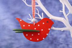 Red bird ornament hanging from white branch. Stock Photos