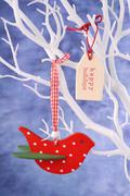 Red bird ornament hanging from white branch. - stock photo