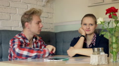 Boy trying to cheer up his offended girlfriend in the restaurant - stock footage
