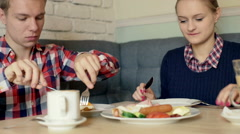 Couple sitting at the table and dish out the food in the cafe Stock Footage