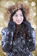 Teenage girl in winter clothes over lights background Stock Photos