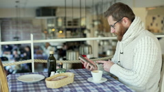 Worried man browsing internet on smartphone in the restaurant Stock Footage