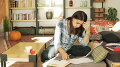 Worried woman working on documents in her living room - stock footage