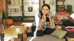 Woman eating apple and chatting on cellphone in her living room Stock Footage