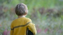 Little Boy Walking Down Dirt Path in Field Away from Camera Stock Footage