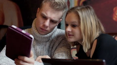 Happy couple browsing internet on tablet in the restaurant Arkistovideo
