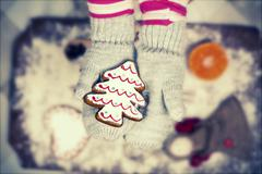 Child holding gingerbread cookies - Vintage Christmas background - stock photo