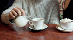 Man sitting in the cafe and pouring milk to his coffee - stock footage