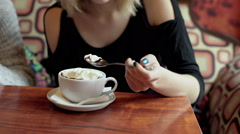 Woman sitting in the cafe and eating mousse from the coffee Stock Footage