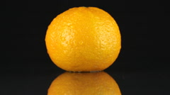 Orange mandarin in drops of dew rotates on its axis Stock Footage