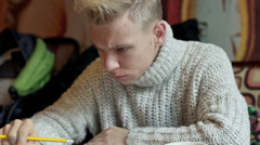 Boy write something in the notebook and checking on tablet, steadycam shot Stock Footage