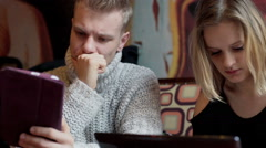 Couple browsing internet on tablet while sitting in the cafe Arkistovideo