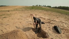 Stock Video Footage of a man digs a hole in the middle of an abandoned wasteland.