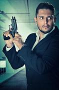 Male agent in an alert position and loading the chamber of his handgun - stock photo