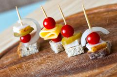 Canape with cherry tomato, cheese and whole grain bread - stock photo