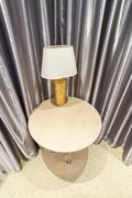 Table lamp by curtains in room - stock photo