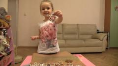 Little girl paints Christmas cookies Stock Footage