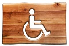 Man on wheelchair sign, symbol of handicapped, disabled person in wooden boar Stock Photos