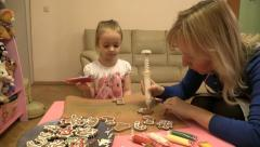 Little girl paints Christmas cookies with her mother. Slider. Stock Footage
