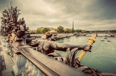 Artistic statue on Pont Alexandre III bridge in Paris, France. Seine river an Stock Photos