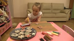 Little girl carefully paints Christmas cookies. Slider. Stock Footage
