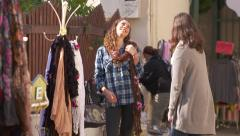Girls shopping and trying on scarf - stock footage