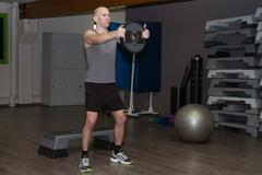 Young  man in sporty outfit raising dumbbells to strengthen his deltoids at f - stock photo
