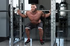 Young Man Doing Exercise Barbell Squat - stock photo