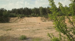 A man digs a hole in the midst of the wasteland. forest around. Panoramic view - stock footage