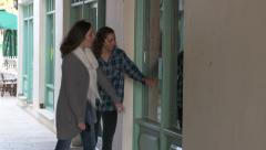 Two girls walking, looking into a display window - stock footage