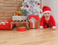 Cute happy little baby boy in Santa suit and old vintage sled with gifts near Kuvituskuvat