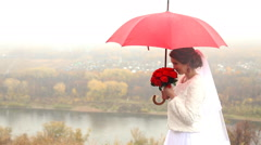 Wedding couple holding red umbrella Stock Footage