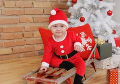 cute happy little baby boy in Santa suit on old vintage sled with gifts near - stock photo