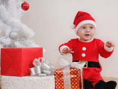 cute happy little baby boy in Santa suit with gifts near Christmas tree - stock photo