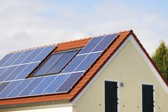 Green renewable energy with photovoltaic installations on the roof - stock photo
