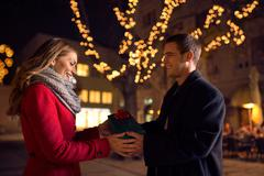 .Beautiful young woman looking at gift box and smiling while her boyfriend gi - stock photo