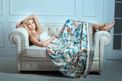Stock Photo of Blonde girl lies on a white sofa.