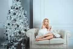 Cheerful girl sitting on a sofa in home comfort. - stock photo