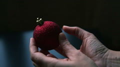 Hands handling a red christmas decorative ball, in a close up Stock Footage