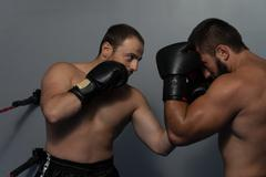 Mixed Martial Artists Fighting - Punching - stock photo