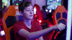 Boy playing on a slot machine simulator races - stock footage