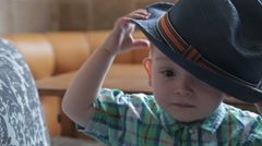 Caucasian baby boy weared a hat sitting on sofa at home Stock Footage