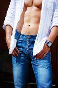 Close-up portrait, man body, dressed in jeans and white shirt, with a clock on - stock photo