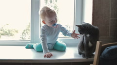 Little boy with black cat sitting near window at home Stock Footage