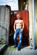 Stock Photo of Sexy fashion portrait hot male model in stylish jeans with muscular body posing