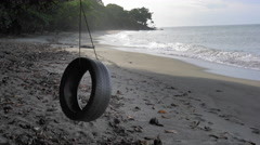 Tyre swing hanging with tree on the beach, Trinidad, Trinidad and Tobago Stock Footage