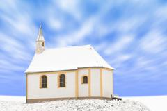 Standing alone detached building of snow-covered small chapel - stock photo