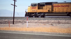 A Freight train enters frame moving fast through the desert. - stock footage