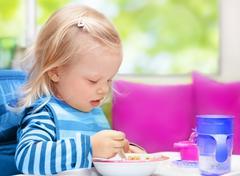 Little baby having breakfast Kuvituskuvat