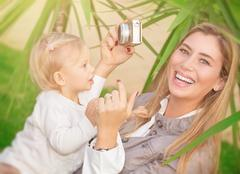 Happy mother photographing baby - stock photo